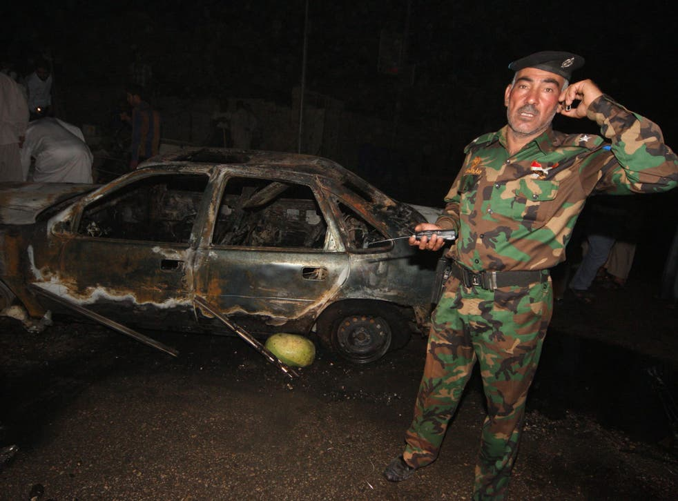 An Iraqi officer inspects the site of a car bomb near Karbala