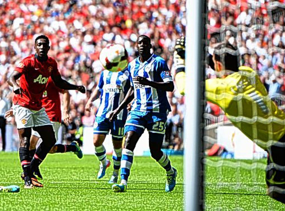 Scott Carson, of Wigan, reacts well to deny Danny Welbeck