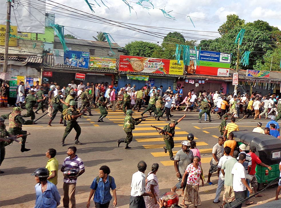 Sri Lankan troops chase local residents protesting against the alleged poisoning of drinking water in the village of Weliweriya in August