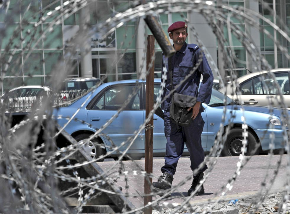 A policeman stands behind razor wire as security is stepped up in Manama