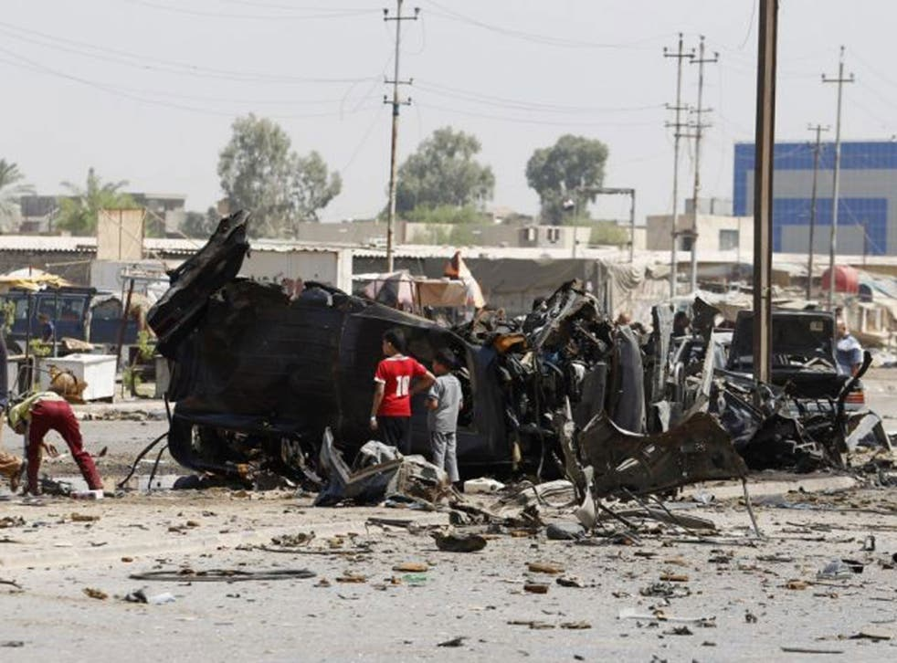 People gather at the site of a car bomb attack in Baghdad, 15 August, 2013. Five car bombs in Baghdad killed at least 23 people on Thursday and wounded more than 80, Iraqi police sources said.