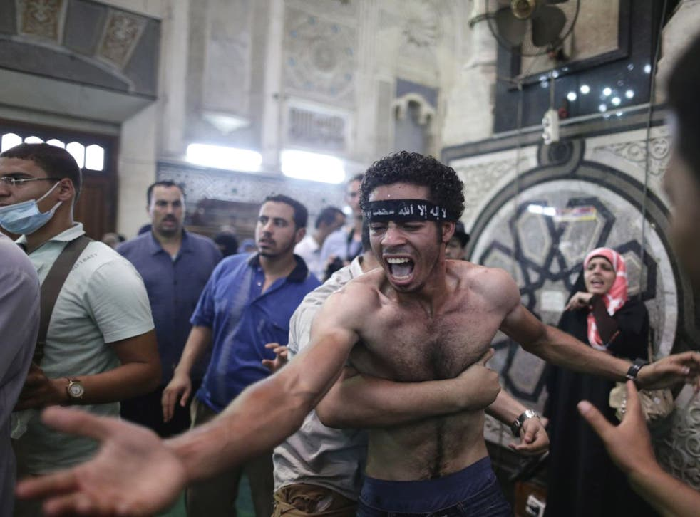 Egyptians mourn over the bodies of their relatives in the Al-Fath mosque