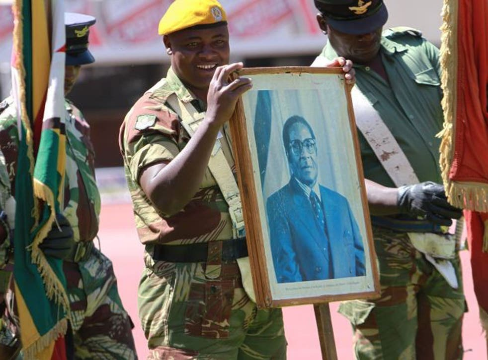 A soldiers holds a portrait of Zimbabwean President  elect, Robert Mugabe  during rehearsals for his inauguration  in Harare, Wednesday, Aug. 21, 2013. Mugabe is expected to be   inaugurated Thursday after Movement For Democratic Change (MDC)  President Morgan Tsvangirai's  case  was dismissed by the Constitutional Court