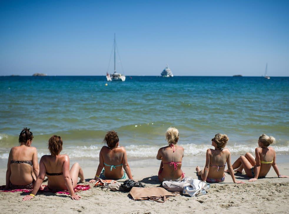 A group of tourists sunbathe at Platja d'en Bossa beach