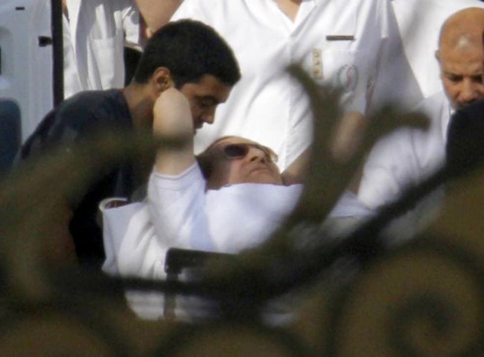 Egyptian medics escort Mubarak  into an ambulance after he was flown by a helicopter ambulance to the Maadi Military Hospital from Torah prison in Cairo