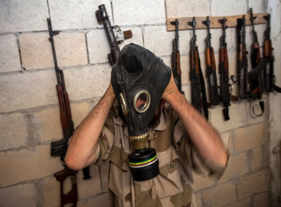 A Syrian rebel tries on a gas mask
