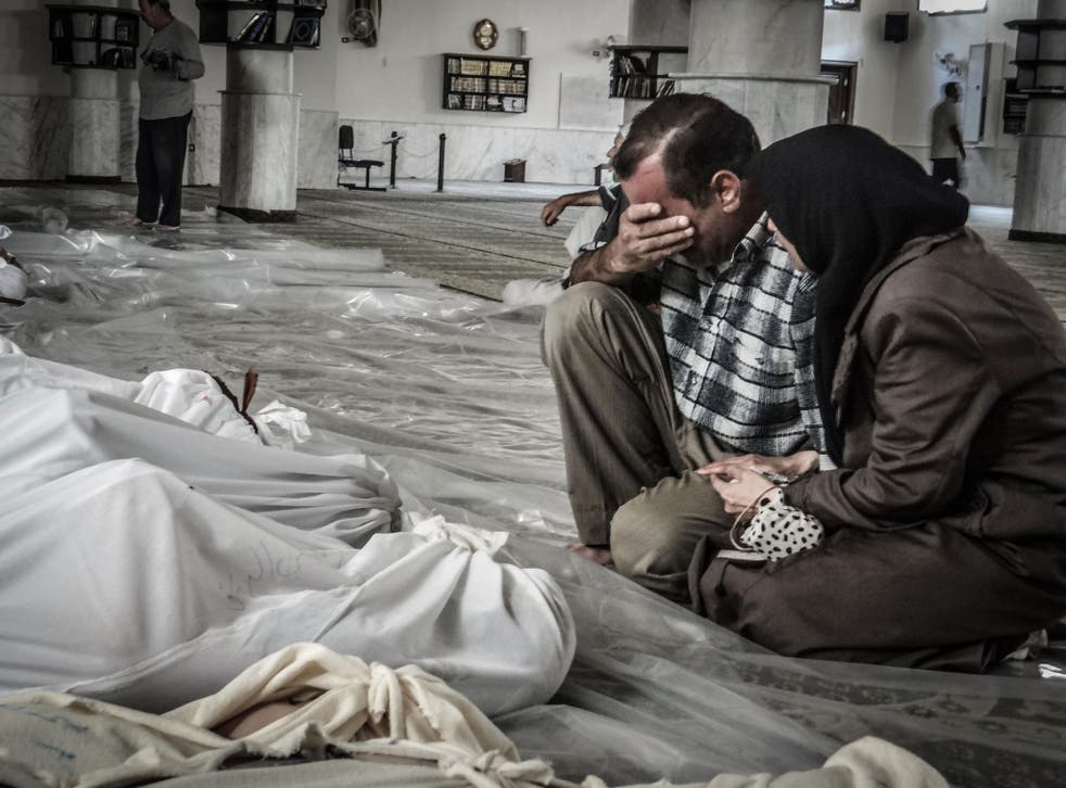 Parents grieve over the body of their child killed in a suspected chemical attack in Damascus