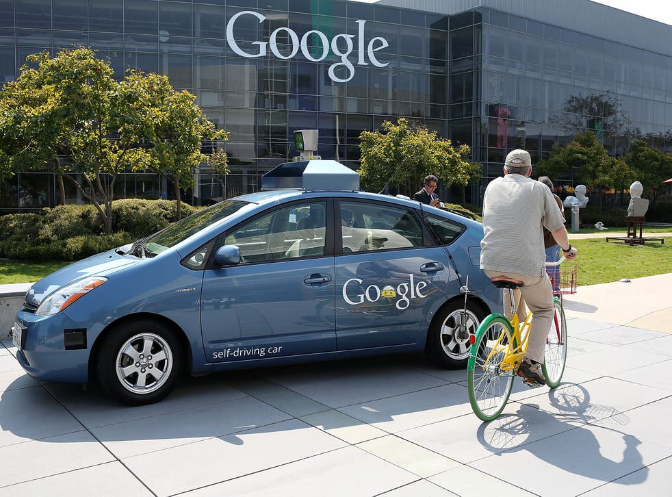 A bicyclist rides by a Google self-driving car at the Google headquarters on September 25, 2012 in Mountain View, California. California Gov. Jerry Brown signed State Senate Bill 1298 that allows driverless cars to operate on public roads for testing pur