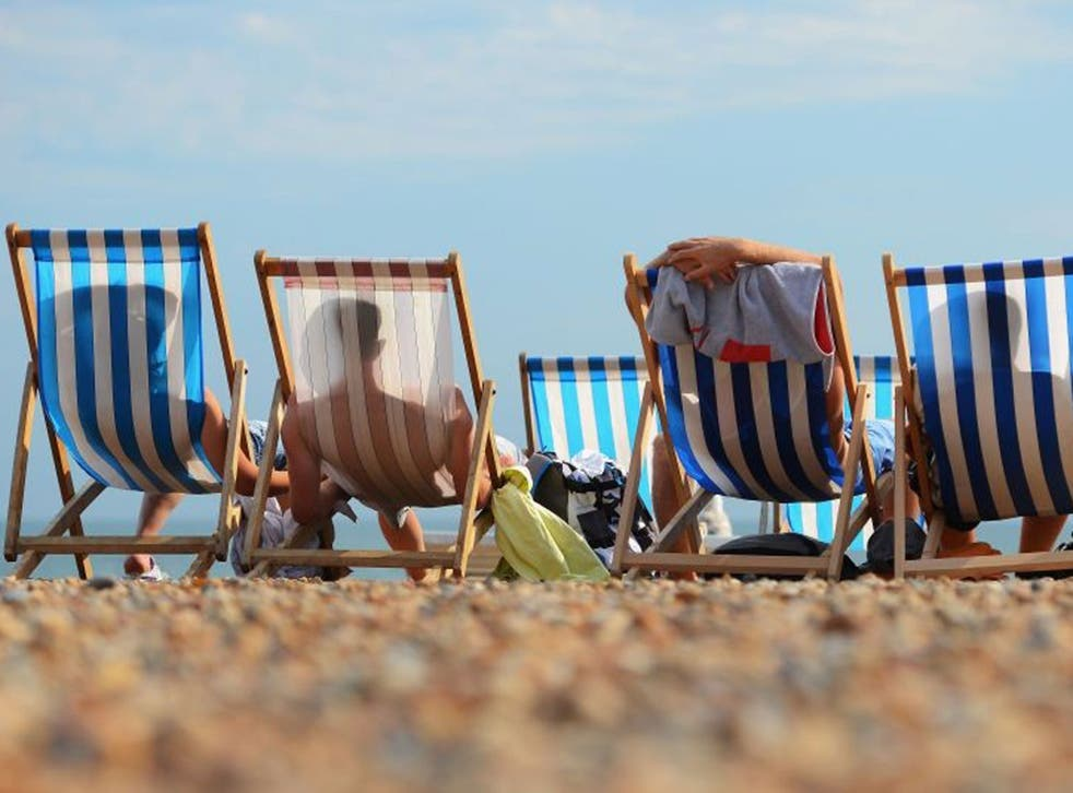 People relax in deck chairs during the hot weather on Brighton beach on 1 August, 2013