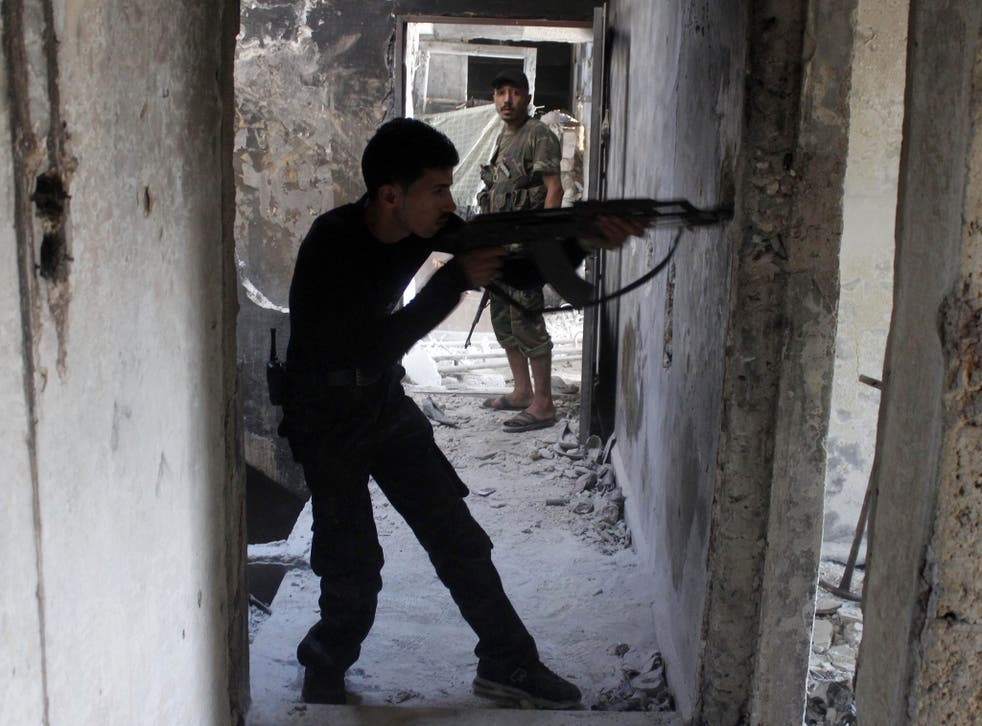 A Free Syrian Army fighter takes up a position inside a building as he points his weapon in the old city of Aleppo
