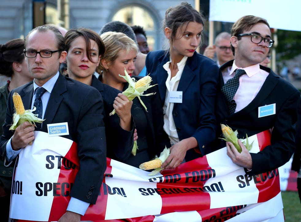 4 September 2013: Environmental activists of 'Friends of the Earth Europe' dressed as bankers hold corn cobs as they demonstrate near the European parliament in Brussels, Belgium