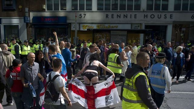 A cross-dressed member of the EDL poses during a rally in London, 7 September 2013