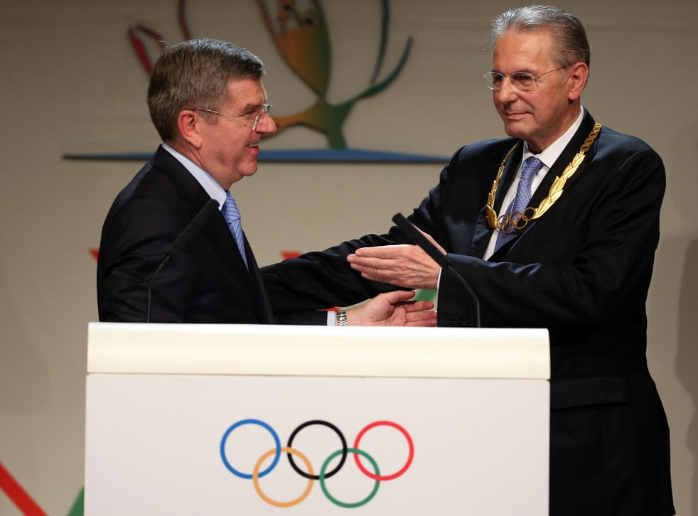President of the IOC Jacques Rogge receives the Olympic Order from newly announced ninth IOC President Thomas Bach