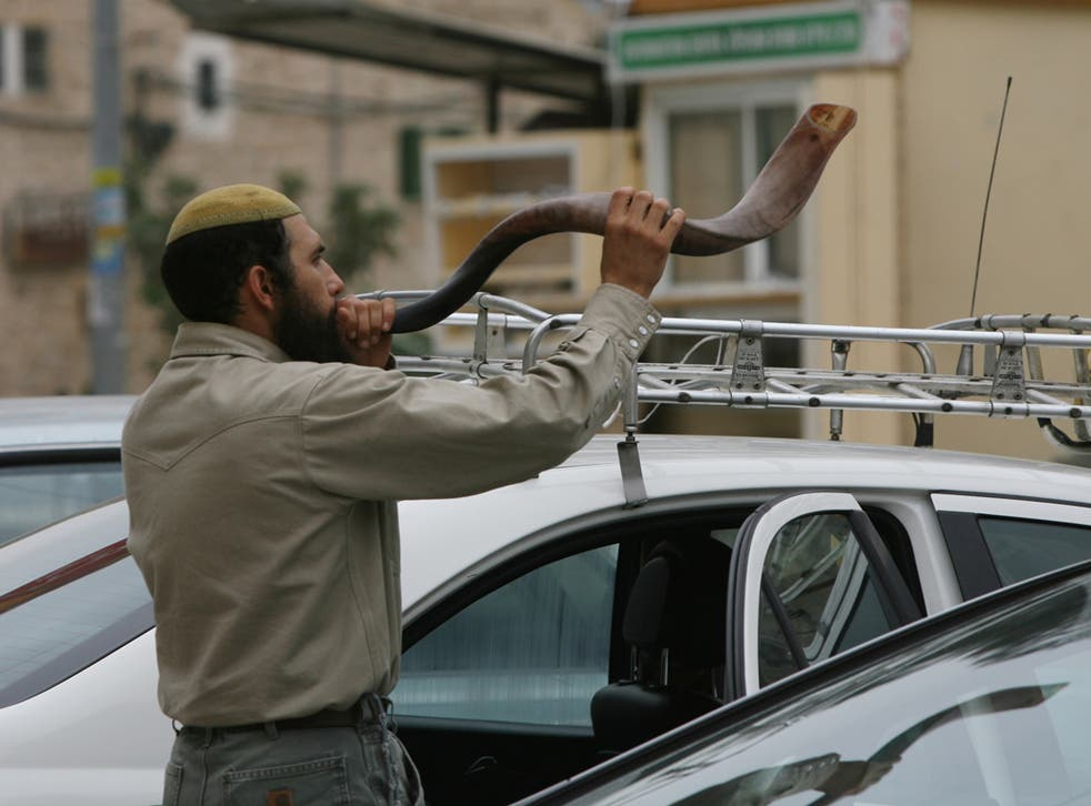 A Jewish settler blows the 'Shofar' horn on the eve of the Day of Atonement, or Yom Kippur