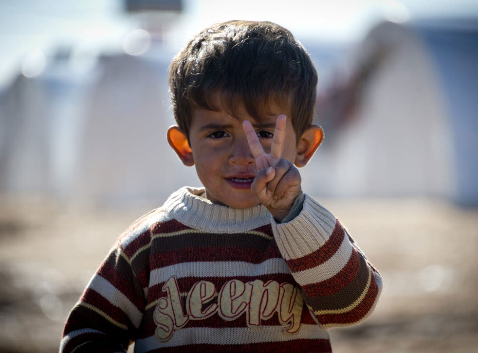Standing in front of a row of plastic tents a young boy flashes the V-sign in a refugee camp on the border between Syria and Turkey near the northern city of Azaz