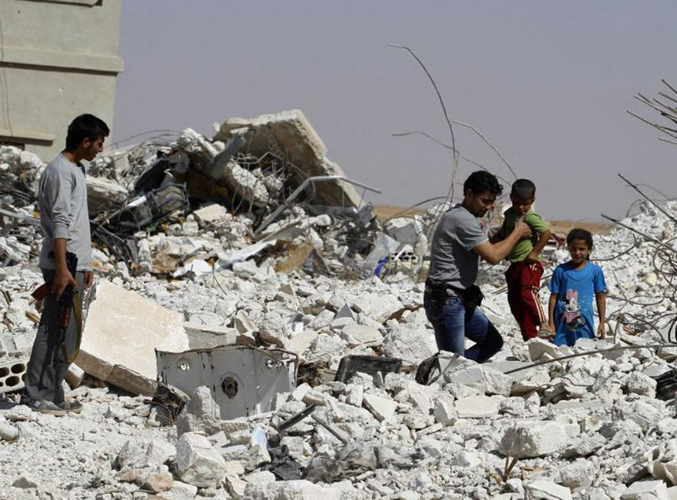 A man helps a boy through rubble in the eastern Hama countryside