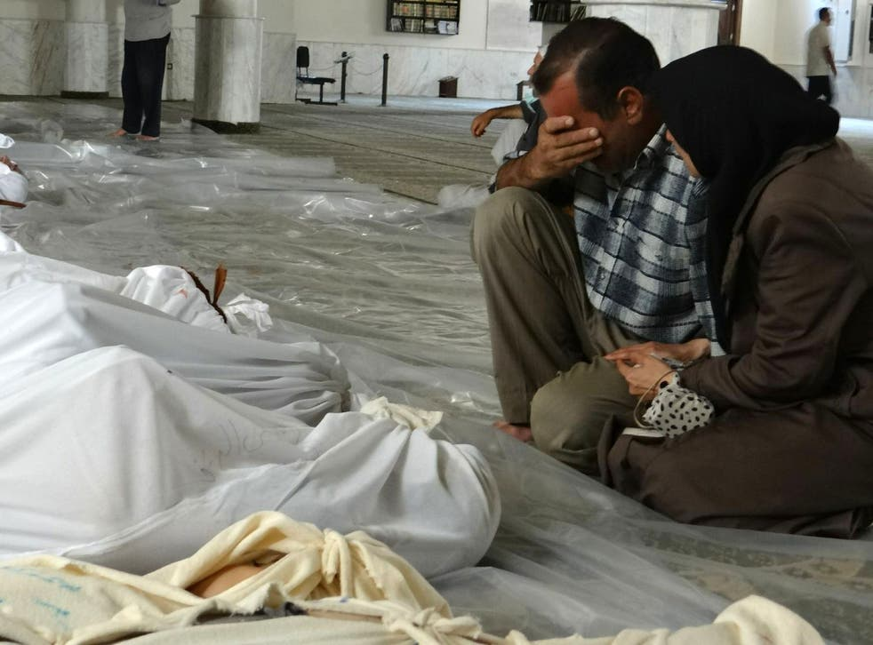 A Syrian couple mourn in front of bodies following what has now been confirmed by the UN as a toxic gas attack