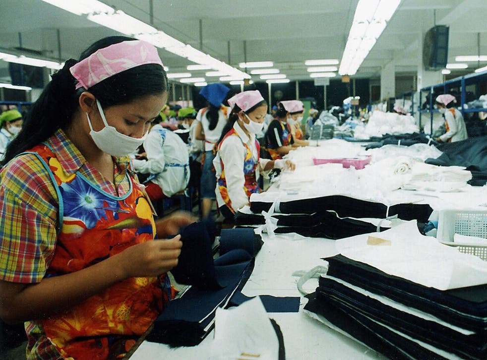 Employees of a garment factory check the quality of stitched garments before packing in the outskirts of the Cambodian capital city Phnom Penh