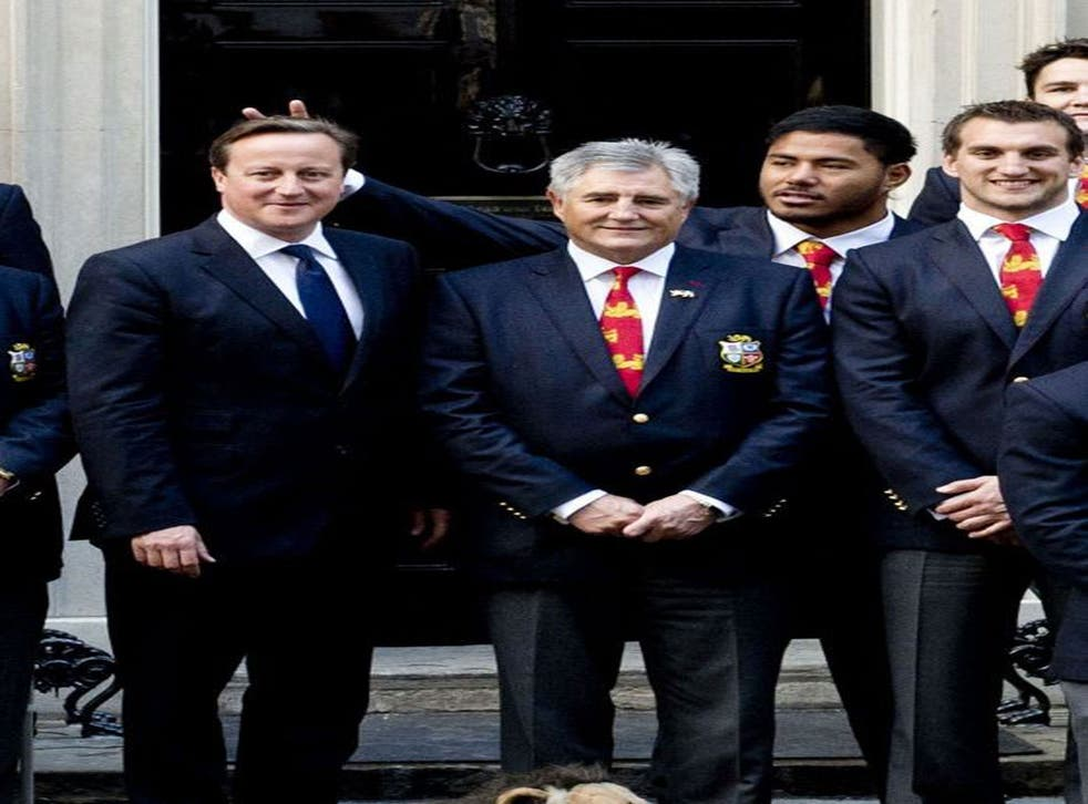 """British and Irish Lions rugby star Manu Tuilagi sticking his fingers above Prime Minister David Cameron's head to give him """"bunny ears"""" during a photo shoot at Downing Street to honour the Lions' victory over Australia."""