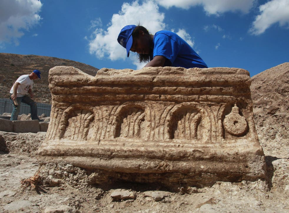 An Israeli Antiquities Authority worker cleans a large carved stone found during excavations of a recently uncovered synagogue on September 13, 2009 at Migdal on the north-western end of the Sea of Galilee in northern Israel.
