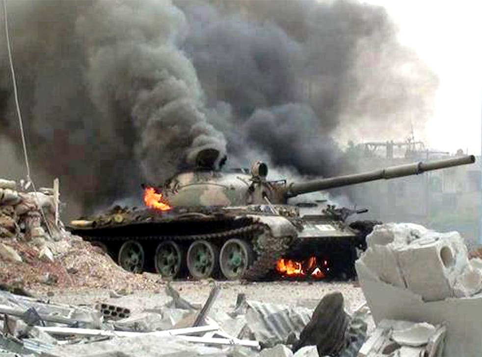A Syrian military tank on fire during clashes with Free Syrian army fighters in Joubar, a suburb of Damascus