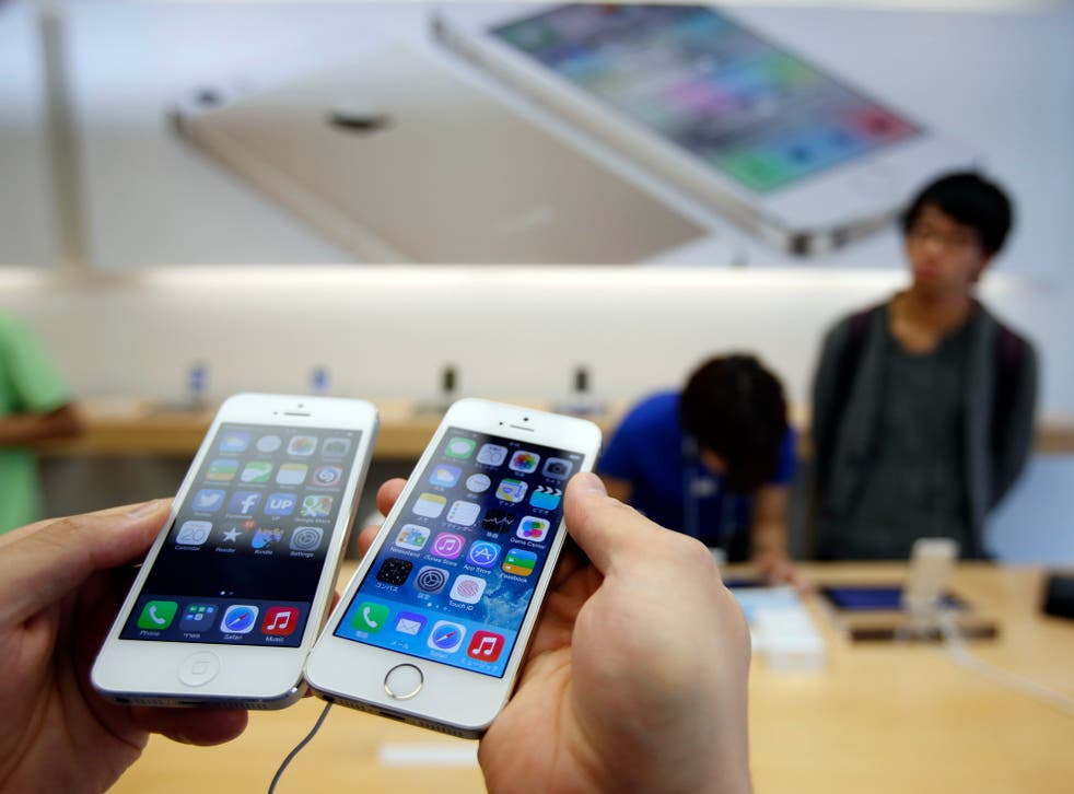 A man holds a new Apple iPhone 5S (R) next to his iPhone 5 at an Apple Store at Tokyo's Ginza shopping district September 20, 2013.