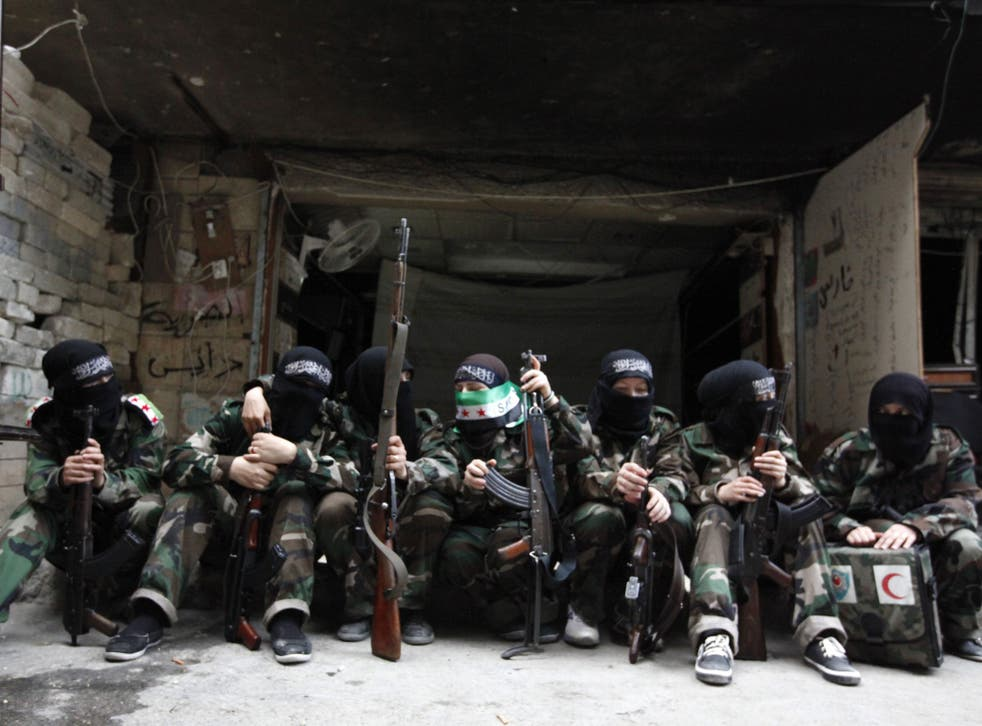 Female members of the 'Mother Aisha' battalion – an all female unit of the Syrian rebels – sit together in Aleppo's Salaheddine district