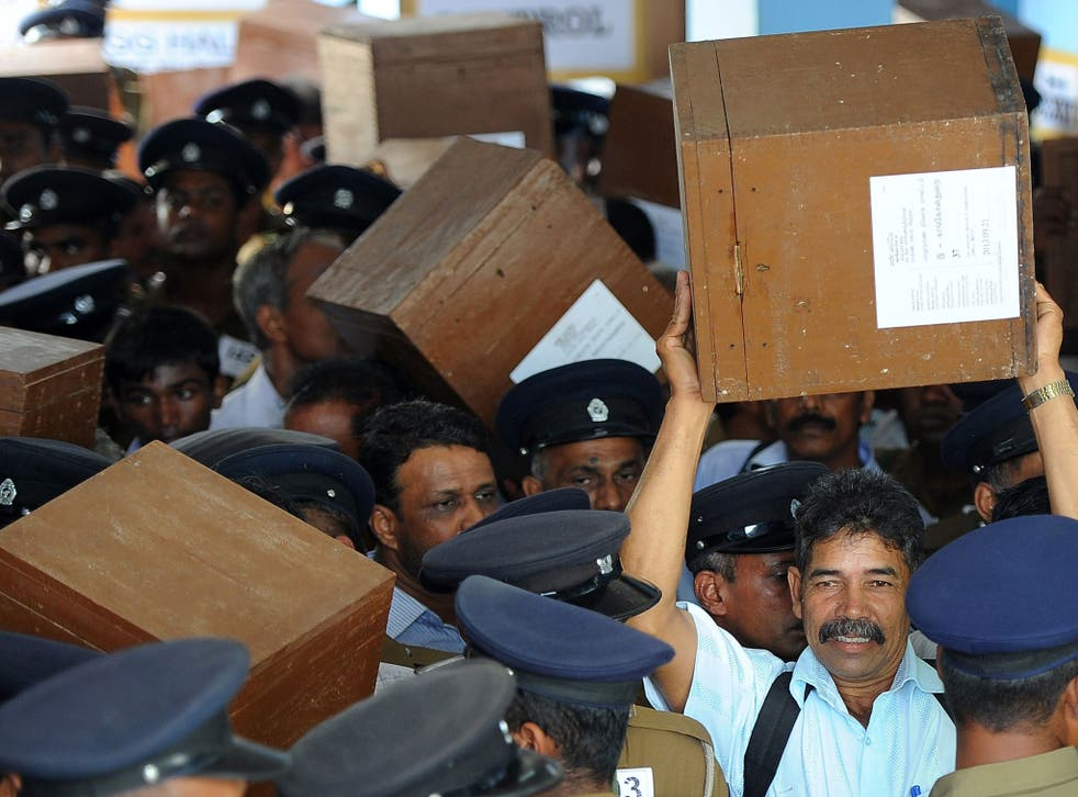 Sri Lankan election workers carry ballot boxes before boarding buses as they prepare to go to their polling centres in Jaffna