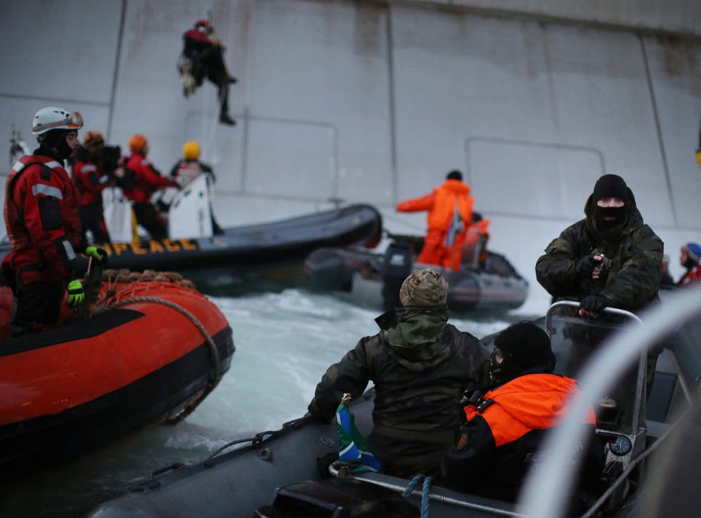 A Russian Coast Guard officer points a gun at a Greenpeace activist as others attempt to climb the Prirazlomnaya oil platform