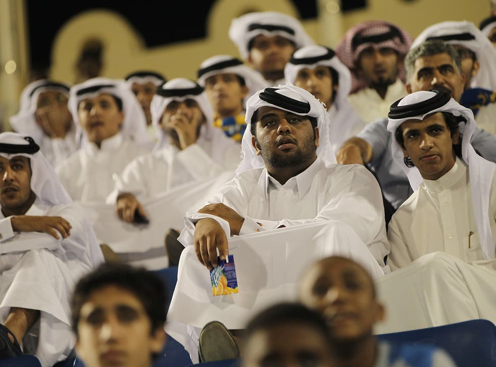 Fans wearing traditional local dress attend the Gharafa vs. Kharaitiyat Qatar Stars League football match at Al Gharafa Stadium on October 23, 2011 in Doha, Qatar. Qatar will host the 2022 FIFA World Cup football competition and is slated to tackle a vari