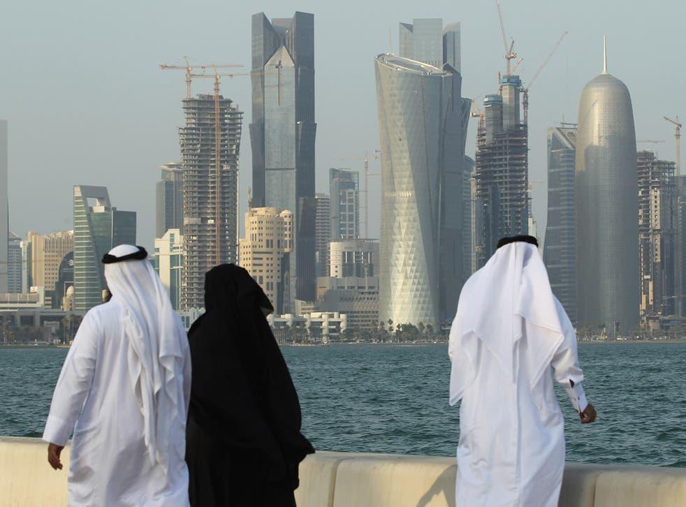 Men and women wearing traditional Qatari clothing visit the waterfront along the Persian Gulf in Doha, Qatar.