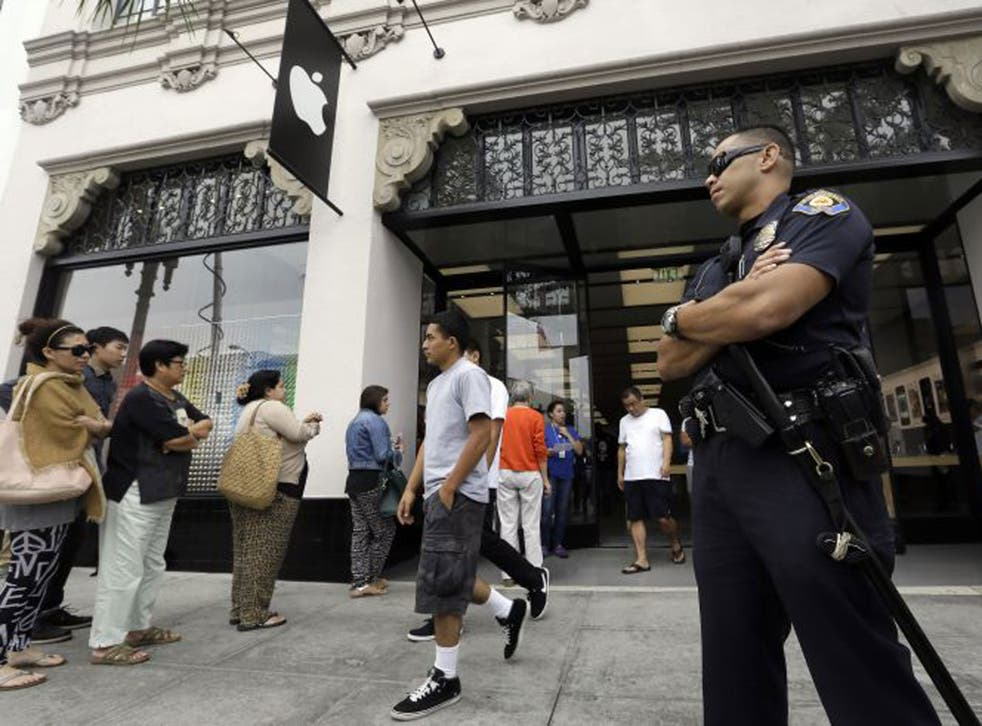 A police officer guards the entrance of the Apple store as customers wait in line for the latest versions of the iPhone during the opening day of sales of the iPhone 5s and iPhone 5C in Pasadena, California