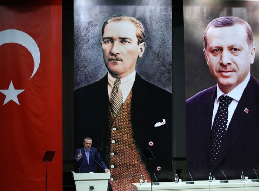 Past glory: Erdogan speaks, backed by portraits of himself and Ataturk, earlier this month