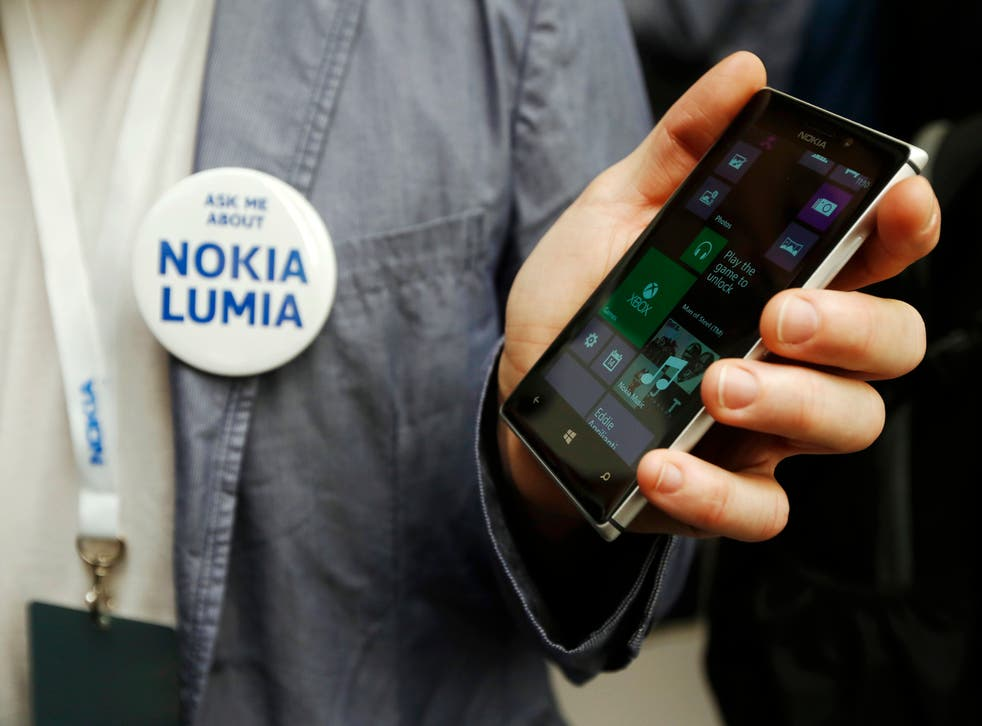 A worker poses with the new Nokia Lumia 925 at its launch.