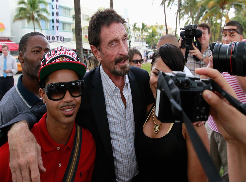 Computer software pioneer John McAfee (C) poses with tourists as he speaks with reporters outside his hotel in Miami Beach, Florida December 13, 2012.