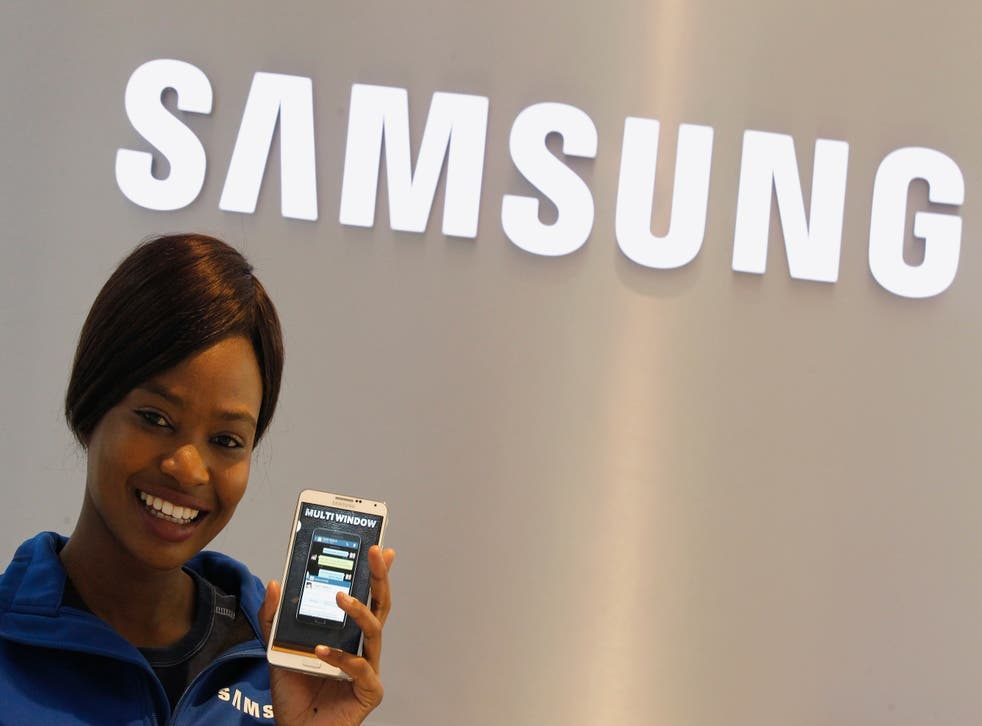A Samsung employee holds a mobile phone at a Samsung display store in Johannesburg, October 3,