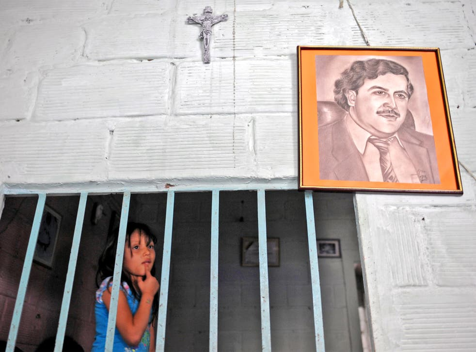 A girl stands by a portrait of Pablo Escobar in Medellin