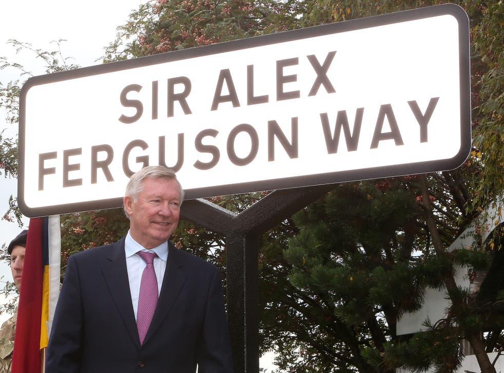 Sir Alex Ferguson poses with the street sign