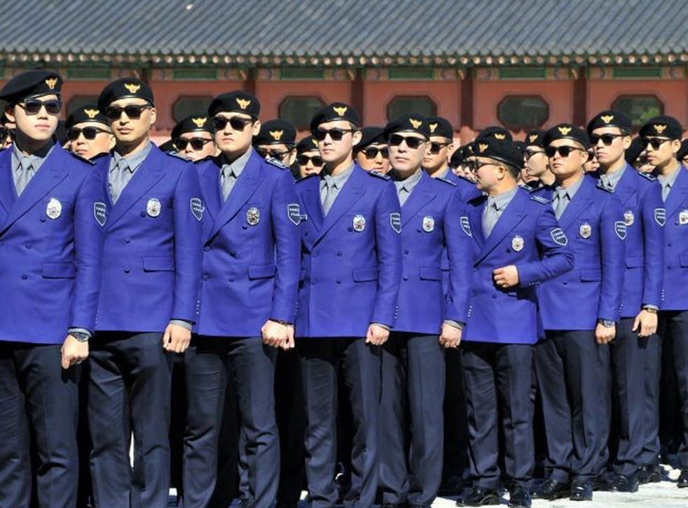 """South Korean """"tourist police"""" officers attend their inauguration ceremony at Gwanghwamun square in Seoul on 16 October, 2013."""