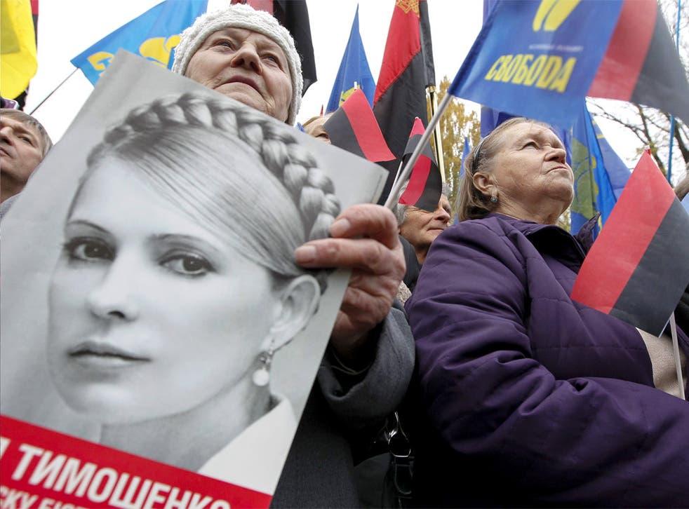 Ukrainians hold Ukrainian Insurgent Army (UPA) flags and portraits of jailed opposition leader Yulia Tymoshenko in Kiev earlier this week