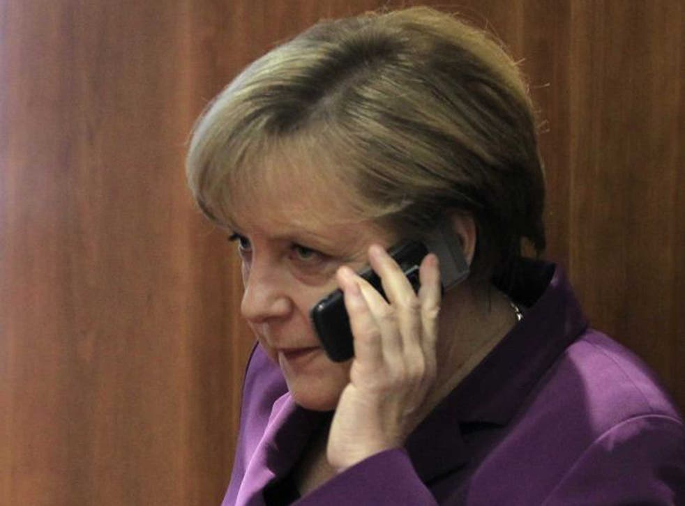 Angela Merkel using her phone two years ago; she is now demanding an apology from Obama after records appear to show the US tapping her calls