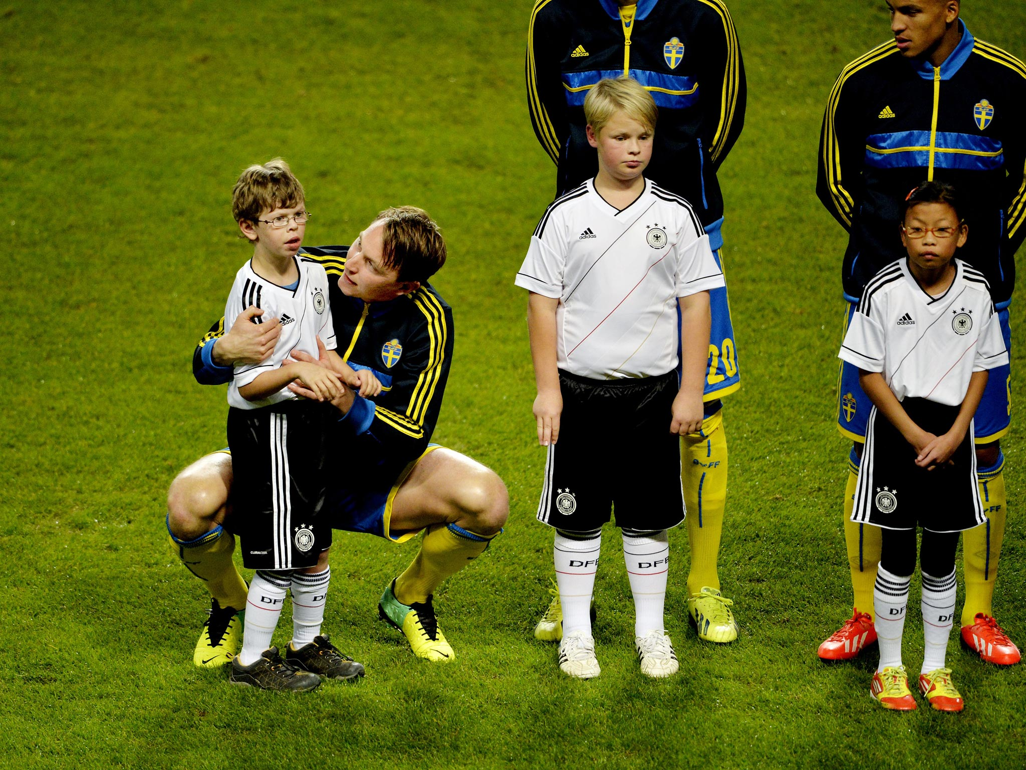 Swedish footballer Kim Källström comforts eight-year-old boy