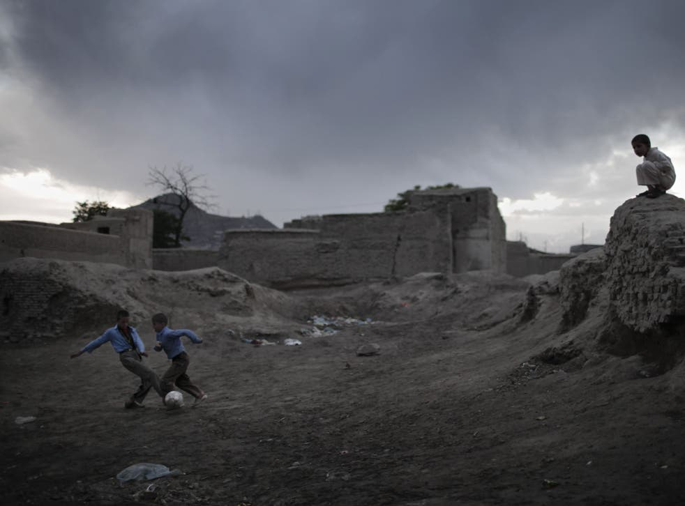 Two Afghan boys play soccer near ruins as the rain approaches at nightfall in the old part of Kabul, on April 10, 2010.
