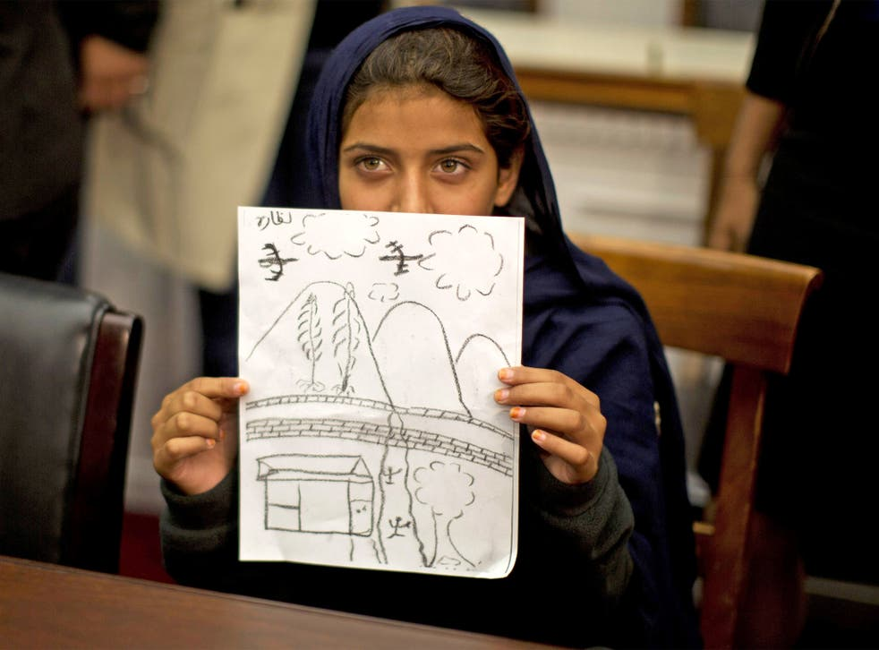 Nabila Rehman holds up a picture she drew depicting the drone strike on her village