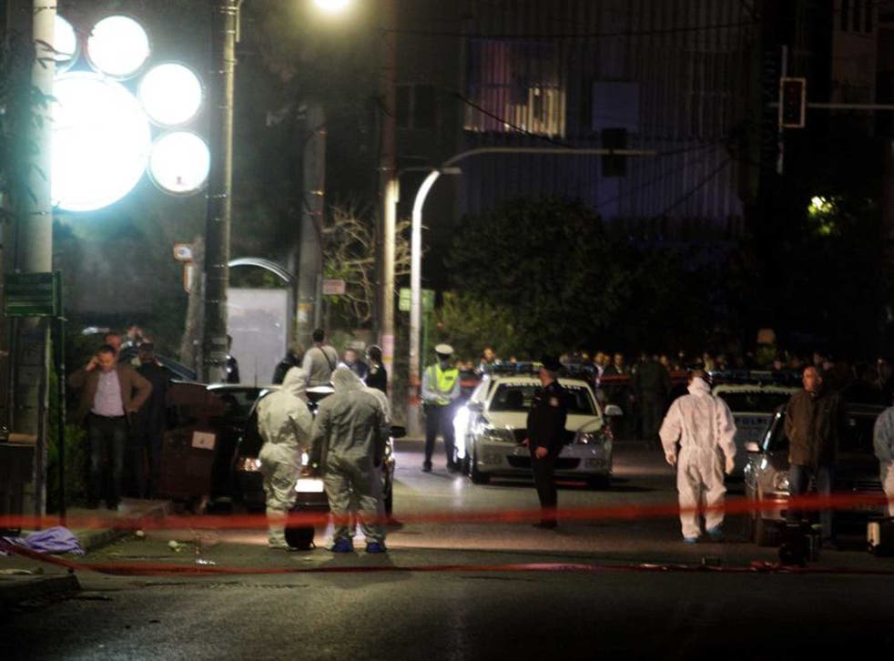 Police officers at the scene of the shooting, outside the local branch of the Golden Dawn party at the northern Athens suburb of Neo Iraklio