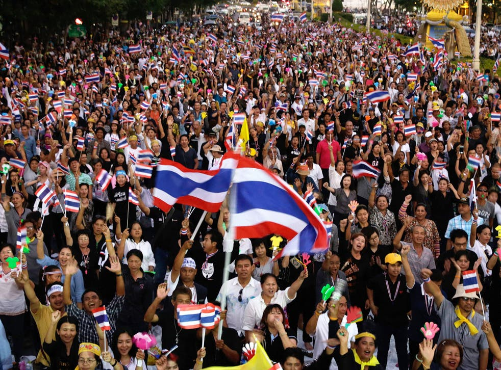 Anti-government protesters wave Thai flags during a rally against a controversial Amnesty bill that passed in Parliament. Protesters fear if the law is passed it could whitewash all crimes for which the former leader Thaksin Shinawatra was convicted