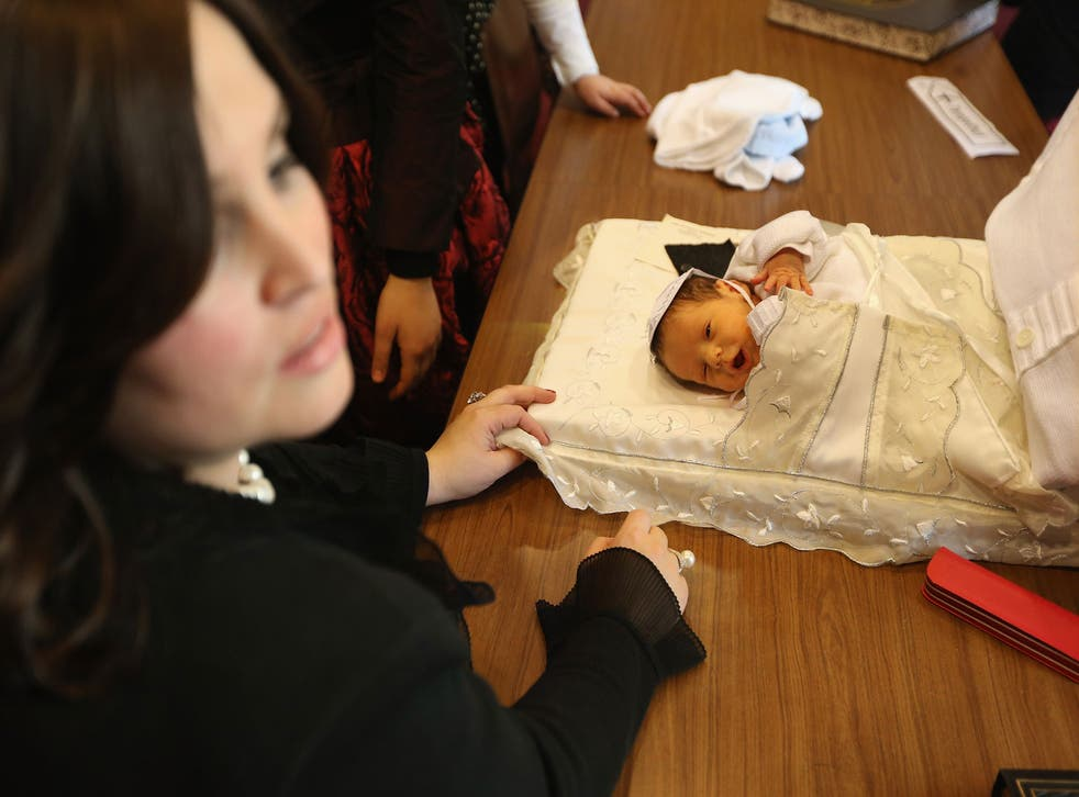 Orthodox Jewish women surround an infant following his circumcision ceremony