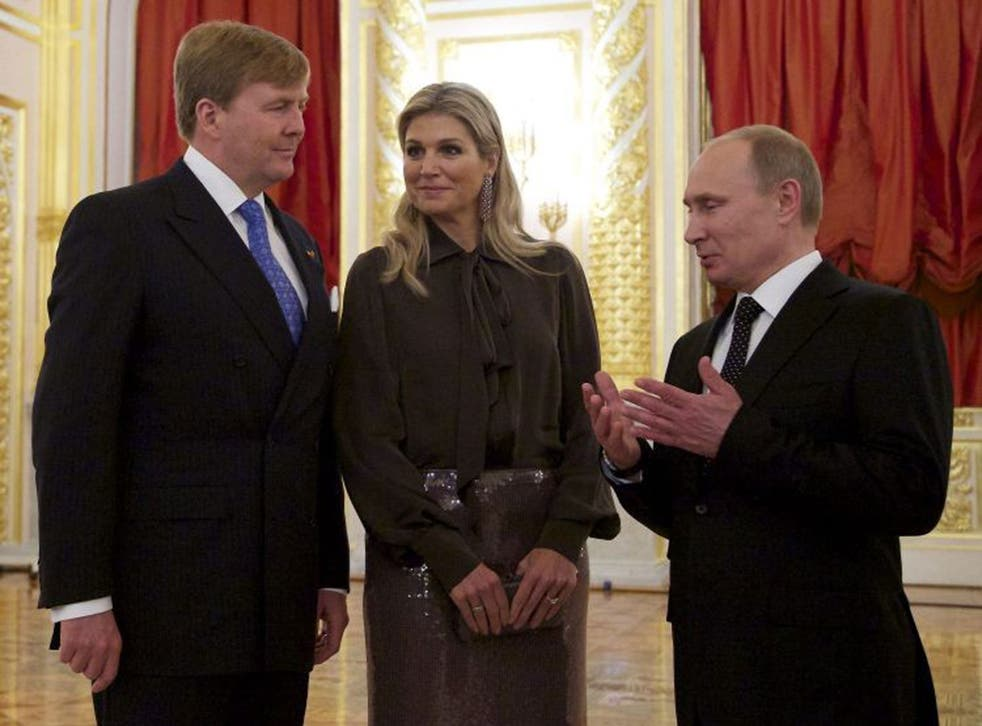 Russian President Vladimir Putin (R) speaking to King Willem-Alexander of the Netherlands (L) and Queen Maxima during their meeting in the Kremlin in Moscow, on Friday
