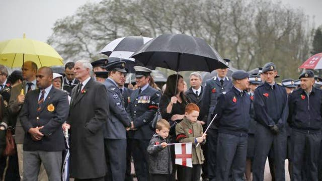Boys play with flags before the funeral of Royal Air Force veteran Harold Jellicoe Percival