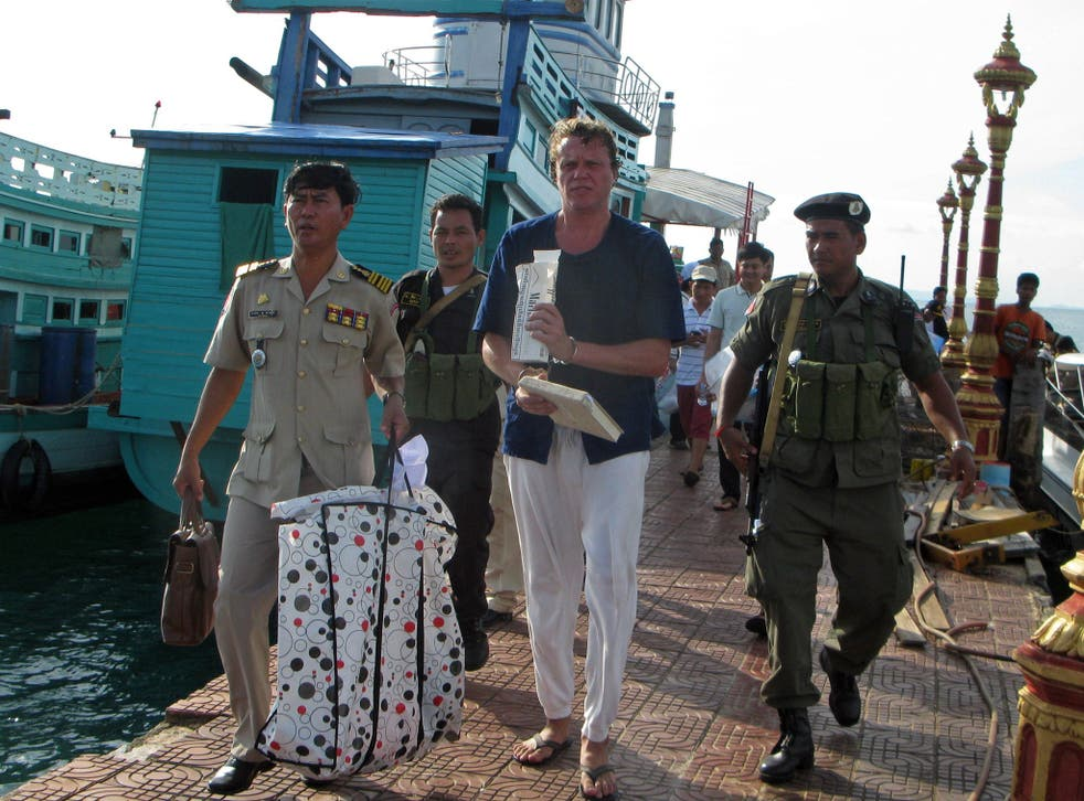Russian tycoon Sergei Polonsky walks along with police officers after his arrest in Sihanoukville, southern Cambodia